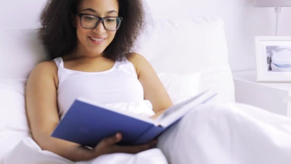 Thumbnail for African Woman Reading Book In Bed At Home Bedroom 76