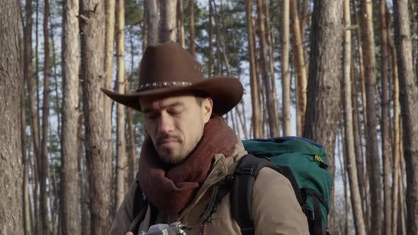 Thumbnail for A Man in a Hat Takes Pictures in the Forest