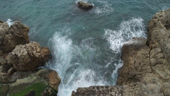 Sea With Waves Breaking And Frothing On a Rocky Beach