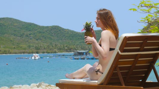 Thumbnail for Woman Drinks Cocktail on the Beach