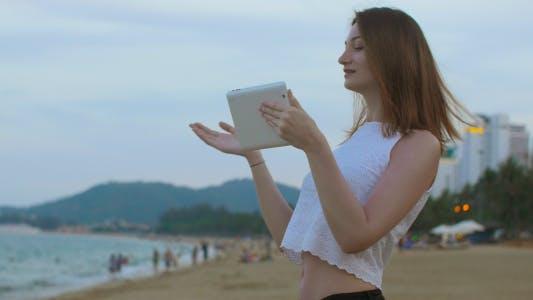 Thumbnail for Girl Talking Using Tablet at Seaside