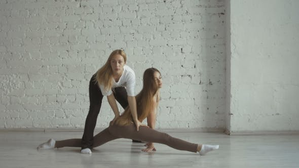 Thumbnail for Yoga Trainer Helps Female Student To Stretch Legs And Do The Splits