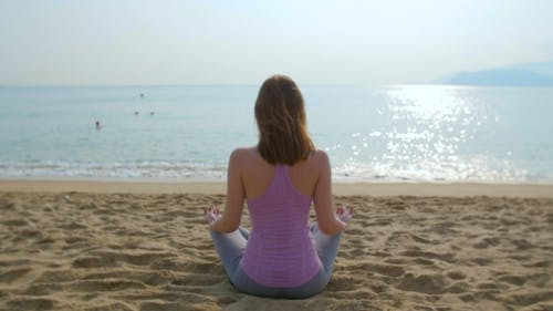 Young Woman Meditate on the Beach