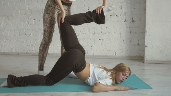 Thumbnail for Yoga Trainer Helps Female Student To Stretch Legs, Sport Practice With Partner