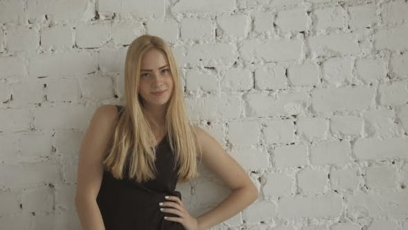 Thumbnail for Smiling Cute Female Blonde Model Looking At Camera On  Brick Wall Background
