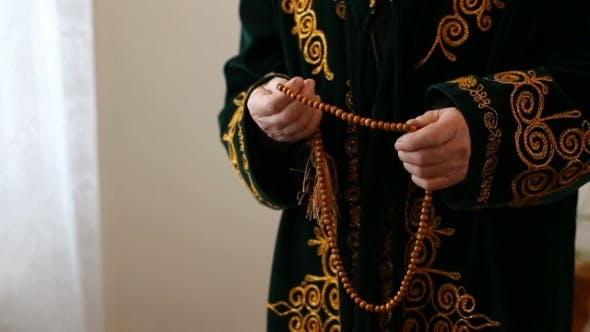 Thumbnail for An Old Man In National Dress Praying With Rosary Beads In Hands