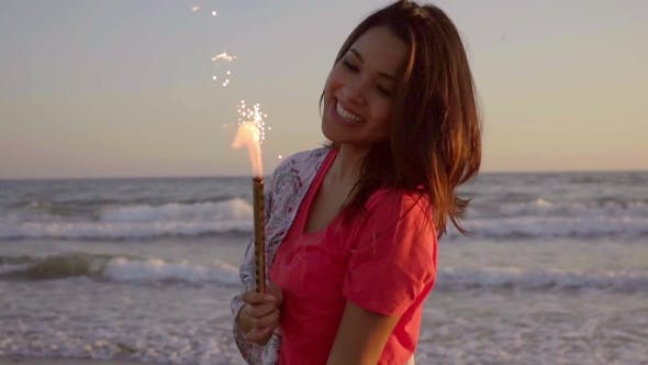 Thumbnail for Brunette Woman With Fountain Candles On The Beach