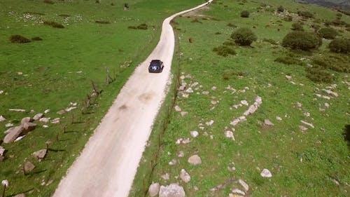 Einziehendes Auto Fahren auf einer kurvenigen ländlichen Straße