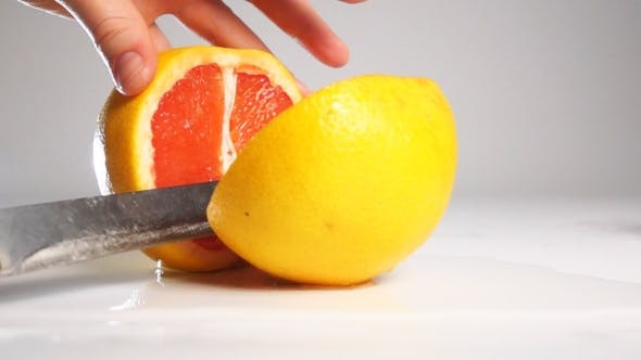 Thumbnail for Cut Grapefruit On White Surface By Knife