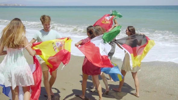 Thumbnail for Group Of Friends Carrying Flags On Sunny Beach
