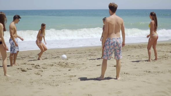 Thumbnail for Group Of Friends Kicking Ball On Sunny Beach