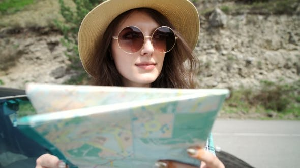 Thumbnail for Travel - Young Woman With Car Look At Road Map On a Beach Against Sea And Sky