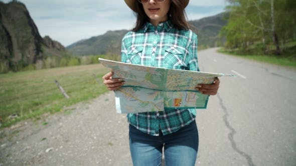 Thumbnail for Happy Young Woman Holding Map On Road