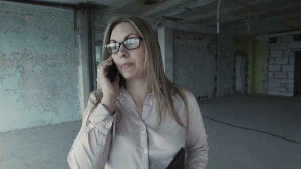 Thumbnail for Beautiful Business Woman Talking On a Smartphone, Going Through Unfinished Rooms Of New Building