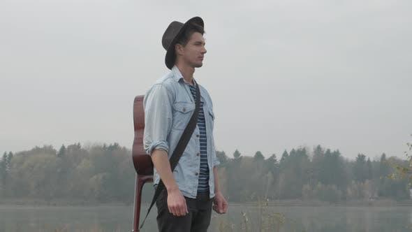 Thumbnail for Hippie Man spielt eine Akustikgitarre im Herbstwald und See