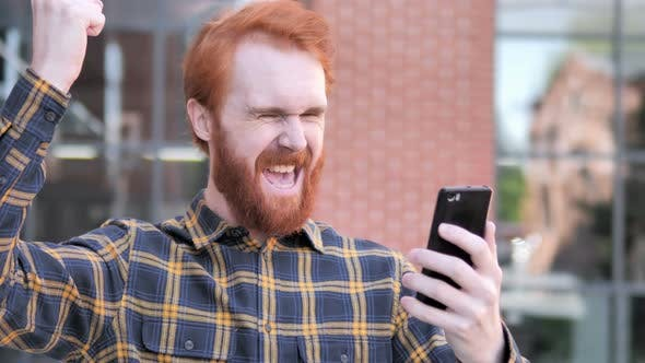 Thumbnail for Outdoor Redhead Man Excited for Success on Smartphone
