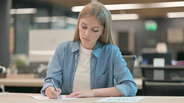 Young Woman Writing on Paper in Office