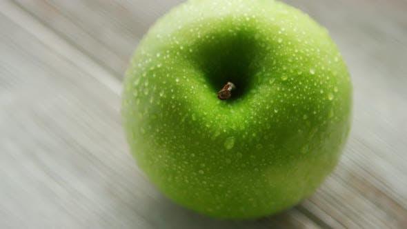 Зеленая спелая яблоко с водяными каплями
