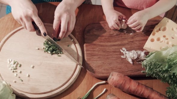 Thumbnail for Mother And Daughter Cutting Onion And Garlic On Wooden Board
