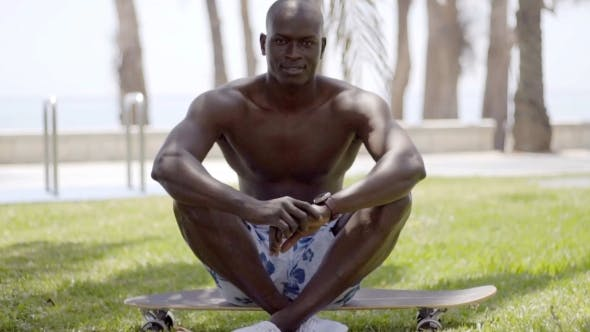 Thumbnail for Handsome Shirtless Black Man sitzend auf Skateboard