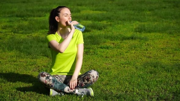 Thumbnail for Running Woman Stopped To Drink Water In The Park. Fitness Girl Training Outdoors