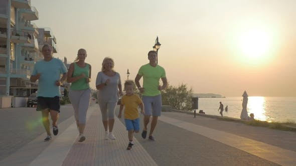 Friendly Family Running To Finish On The Pavement At Sunset