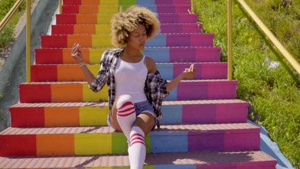 Thumbnail for Jaunty Young Woman Sitting On Rainbow Steps