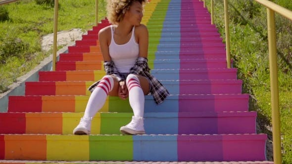 Thumbnail for Young Woman Sitting On The Colorful Stairs.