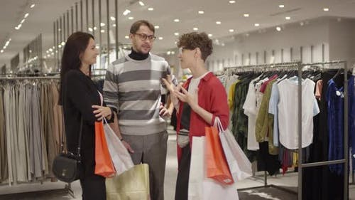 Women and Man with Shopping Bags Chatting in Store