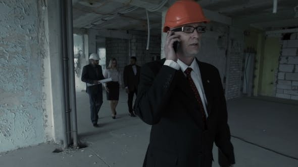 Thumbnail for Man In Suit, Helmet Call Inside Construction Site. At Background Team Of Young Builders Man, African
