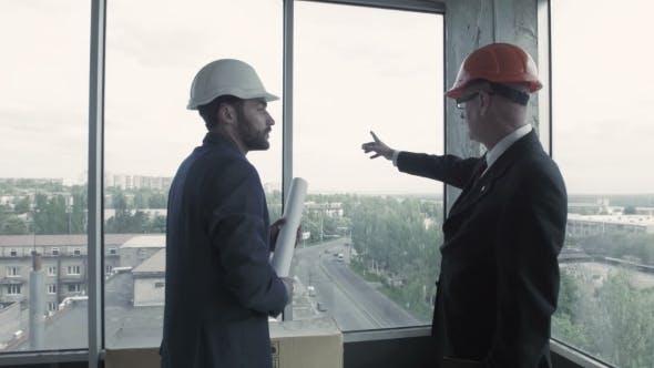 Thumbnail for Zwei Männer in Anzug und Helm diskutieren Blaupause, berechnen und kommunizieren mit Kollegen. Amerikanische