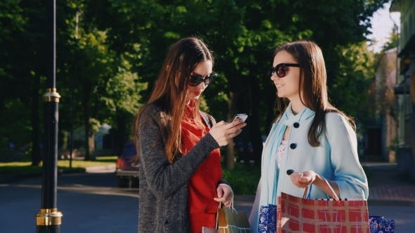 Thumbnail for Two Girl Friends With Shopping Bags Used Smartphone Outdoor