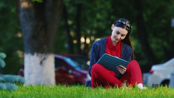 Thumbnail for Internet And The Device Is Always With You. Woman Enjoys The Tablet Outdoors