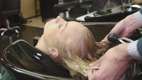 Professional Barber Rub Shampoo In Hair Of Blonde Young Girl