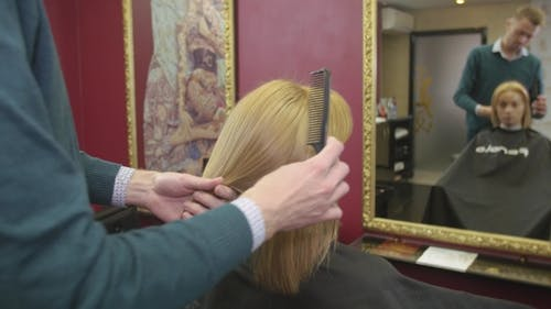 Professional Barber Comb Dry Hair To Blonde Girl By Straight Comb In Beauty Saloon. Mirror.