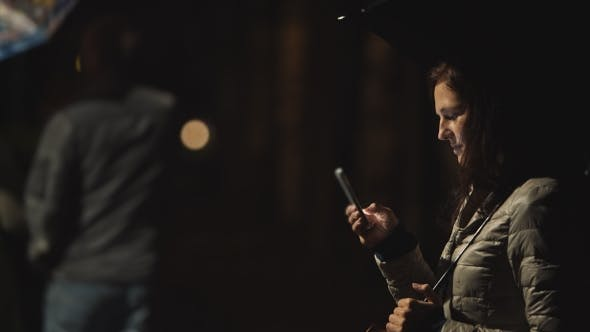 Thumbnail for Girl With Umbrella Uses Her Mobile Phone At Night On The City Background