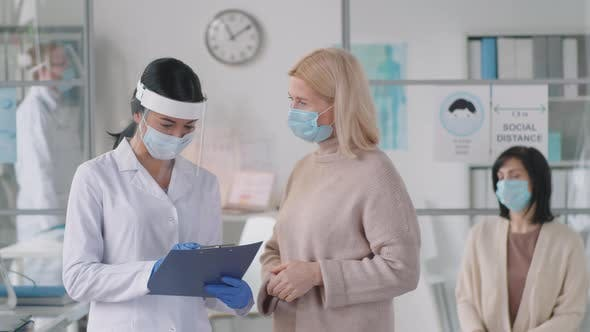 Woman Speaking with Female Doctor in Protective Uniform