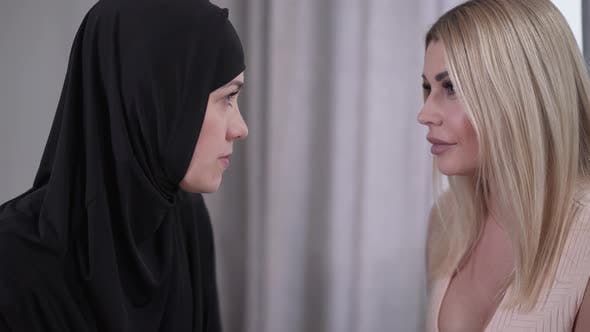 Cover Image for Close-up Faces of Two Women Looking at Each Other. Portrait of Modern Caucasian Gorgeous Lady and