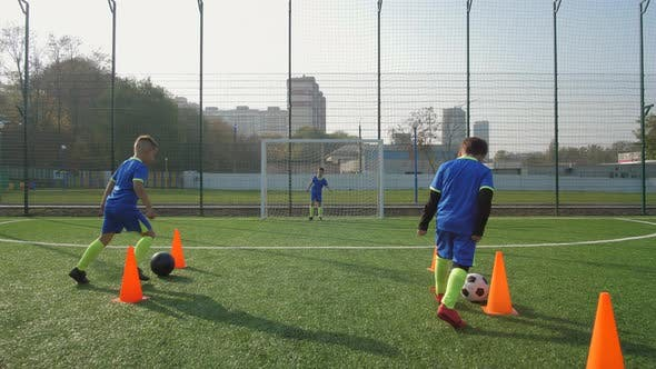 Cover Image for Young Football Players Training To Score Goals