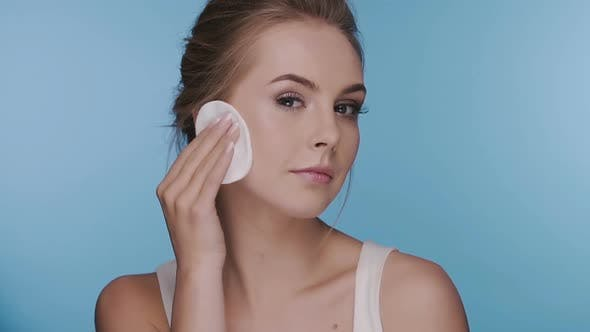 Thumbnail for Happy Girl Wiping Her Face with Cotton Pad on Blue