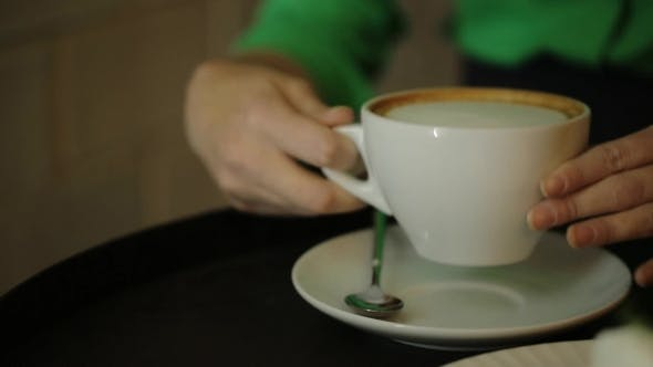 Thumbnail for The Woman Sitting At The Table Is Moving The Cup Of Coffee Up And Down Drinking The Cappuccino