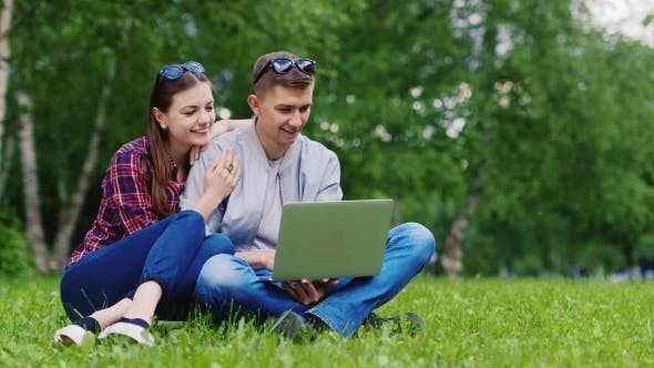 Thumbnail for Attractive Couple Relaxing In The Park, Sitting On The Lawn And Enjoy Laptop