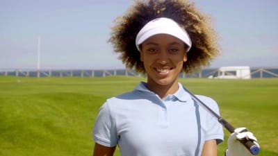 Cheerful Female Golfer Walking With Golf Club