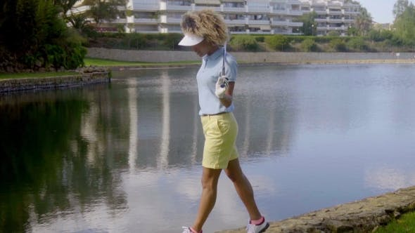 Thumbnail for Woman Golfer Walking Beside a Lake