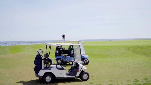 Cover Image for Two Golf Carts With Golf Bags On a Golf Course