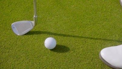 Head Of a Golf Club With a White Golf Ball