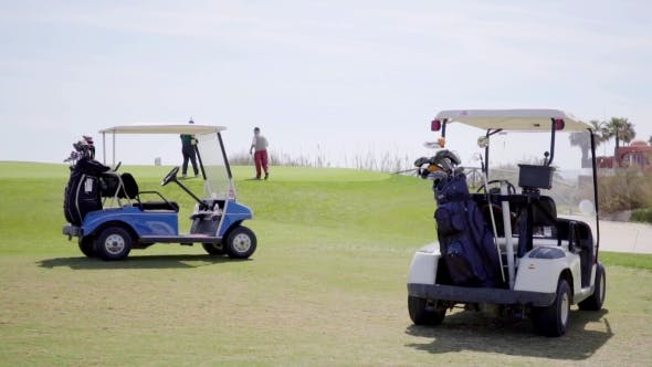 Thumbnail for Two Golf Carts Loaded With Bags And Equipment