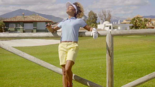 Thumbnail for Attractive Young Woman Golfer Leaning On a Fence