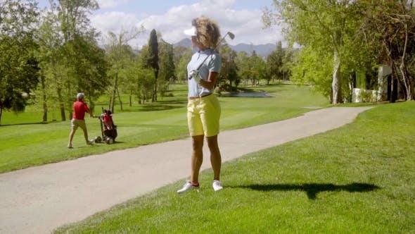 Thumbnail for Woman Golfer Watching a Man Pushing a Golf Cart