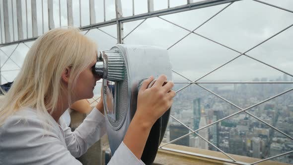Thumbnail for Side View: Blonde Woman Looking Through Binoculars on the Panorama of New York. Visit New York